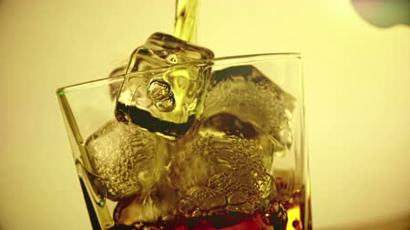 single shot : barman pouring whiskey in the glass with ice cubes on wood table background, focus on ice cubes, whisky relax time, gold warm atmosphere Stock Footage