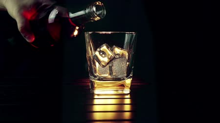 single shot : barman pouring whiskey in the glass with ice cubes on wood table and black dark background, focus on ice cubes, whisky relax time on warm atmosphere Stock Footage