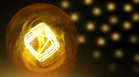 construído : turn on and turn off in slow motion, retro vintage light bulb with old technology with filament built-in with warm light yellow tint and gold bokeh background, concept of christmas and happy new year