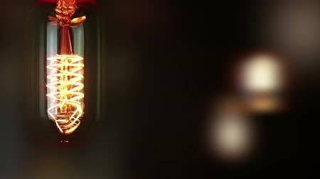 construído : turn on and turn off in slow motion, retro vintage light bulb with old technology with filament built-in with warm light yellow tint and black background with unfocused retro bulbs, vintage object Stock Footage