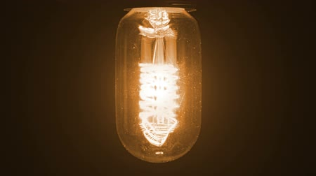 construído : turn on and turn off in slow motion, retro vintage light bulb with old technology with filament built-in with warm light yellow tint and black background, vintage object old style Stock Footage