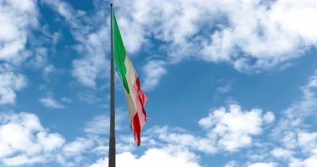 itália : waving fabric texture of the tricolor flag of italy on blue sky with white clouds, moving on the wind, patriotic