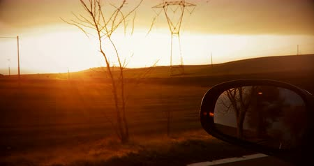 side road : shot on a rear view mirror of a sunset with nature in background, concept of environment and