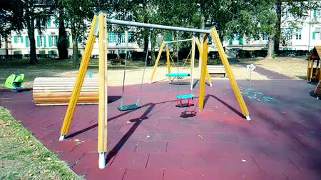 recess : empty swings with chains swaying at playground for child, moved from wind, shot in slow