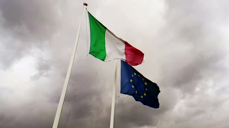 italiaanse vlag : waving fabric texture of the flag of italy and union europe on sky with clouds, concept of business and Stockvideo