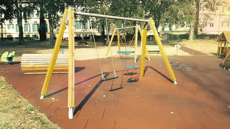 детская площадка : empty swings with chains for children, moved from wind, shot in slow