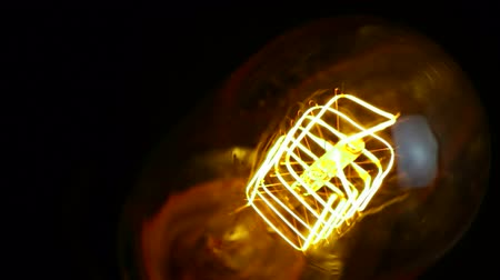 construído : turn on and turn off, close-up of retro vintage light bulb with tungsten technology built-in on black background, old style atmosphere