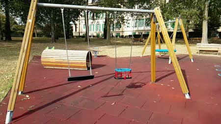 üres : empty swings with chains swaying at playground for child, moved from wind, shot in slow