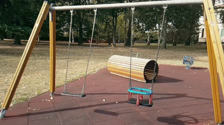 üres : empty swings with chains for children, moved from wind, shot in slow