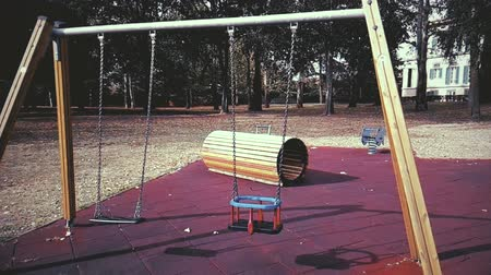 plac zabaw : empty swings with chains swaying at playground for child, moved from wind, shot in slow