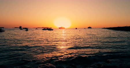 winch : Famous, beautiful beach at sunset with calm sea near Café del Mar, in summer very popular, sandy coast have a fantastic view of island of ibiza. Moored vessels on bay. Ibiza Island, Balearic Islands.