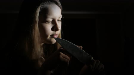 coltello : Ragazza teenager con un grosso coltello, film horror scena scura, 4K UHD