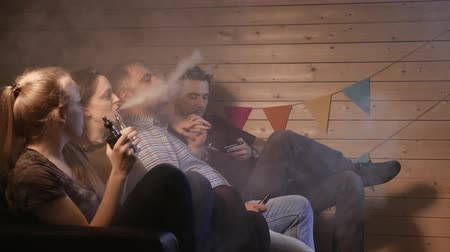сорняки : A group of people vaping, inhaling and exhaling large clouds of smoke and having fun together.  Company of good friends. 4K UHD.