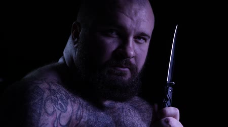 meth : Bald tattoed bearded muscular gangster with a knife. 4K UHD
