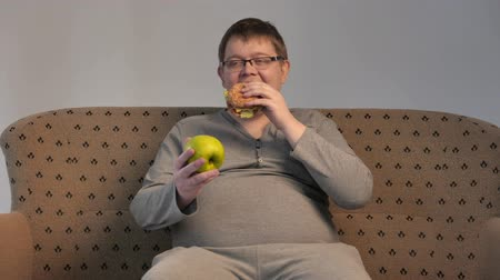 rosto humano : Lonely fat guy eating hamburger. 4K UHD