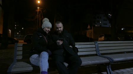 прижиматься : Couple sitting on the bench at night Стоковые видеозаписи