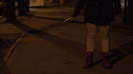 bloodshed : A knife in a hand of a woman. Night street slow motion