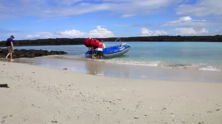 equador : Crew member unloading life vests from the dinghy at Chinese Hat island, Galapagos National Park, Ecuador