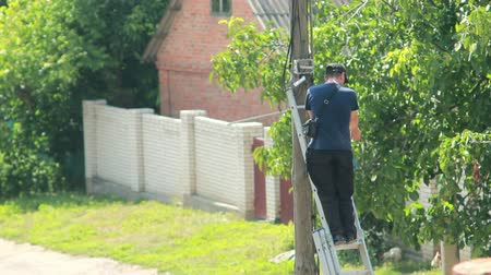 elektryk : man working with the equipment on the pole