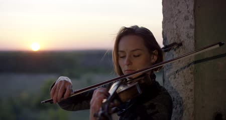 lesson : Playing violin in ruined building with sunset 4K.