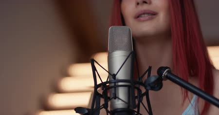 Beautiful young woman recording a song in a professional studio. Sexy girl posing and dancing