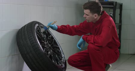 The car washer is washing the wheel with brush carefully slowmotion