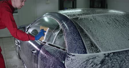 wiper : Manual car washing with sponge slow-mo - Hand spreads foam on vehicle doors slow motion Stock Footage