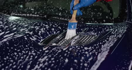 arruela : Using a foaming brush washer at a manual car wash. Car detailing.