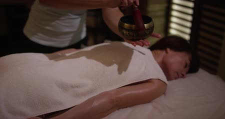 singing bowl : FEW SHOTS. Massage therapist plays on the singing bowl on womans belly in spa center. Body care, skin care, wellness, wellbeing, beauty treatment concept. Slow motion Stock Footage