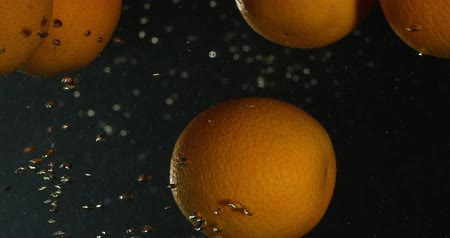 pulverização : Orange Drops Under Water on Black Background. Fresh Orange Fruit Plunging And Splashes Water. Water Air Bubbles Stock Footage