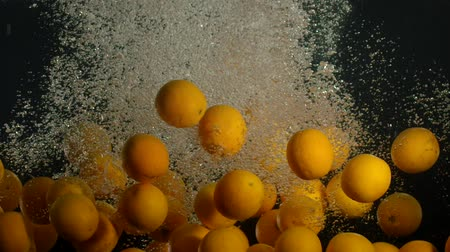 plunging : Orange Drops Under Water on Black Background. Fresh Orange Fruit Plunging And Splashes Water. Water Air Bubbles Stock Footage
