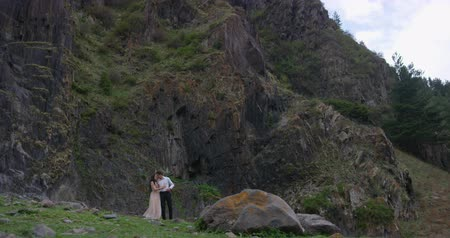 Romantic couple embraces on the edge of the mountain