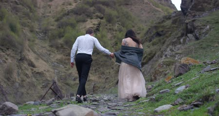 Back view. Couple walking on the mountain range.