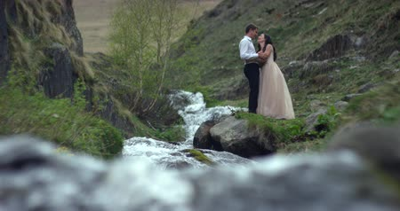 Young beautiful wedding couple standing near the waterfall. Wedding day. Slow motion Wideo
