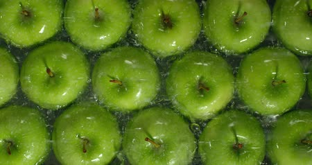 Fresh Green Apples being washed by water. Washing Fruits.