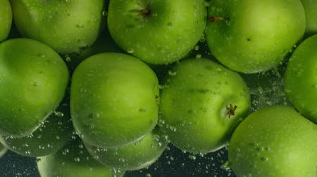 apple sign : Green apples fall down in water against black background, super slow motion