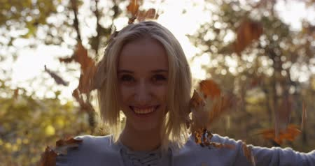 socialization : Young woman tossing up leaves in autumn forest park Stock Footage