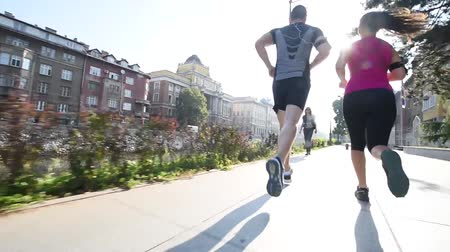 morning : healthy couple jogging in the city streets at early morning with sun flare in background