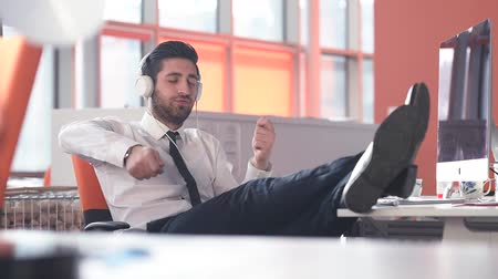 релаксация : happy young startup business man listening music on phones and hold legs on table while playing guitar with hands