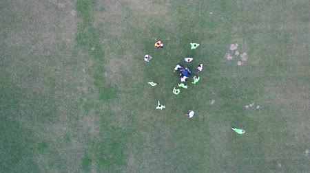 penas : Injuried soccer player laying on ground while medical support staff helping. Team players waiting and resting . Aerial flat lay flaying above top view  footbal game break Stock Footage