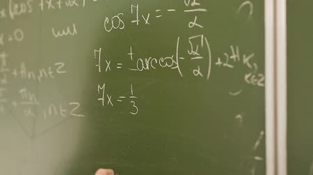 zpátky : Student writing mathematical formula on blackboard