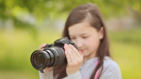 képek : Small girl takes pictures on camera. Stock mozgókép