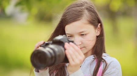 obrázky : Small young girl takes pictures on camera