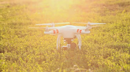 взятие : Work propellers quadrocopters standing on the grass in evening sunshine Стоковые видеозаписи