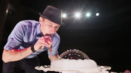 рекламный : The man the actor creates figures from soap bubbles and blows a smoke from them. Soap bubbles show.