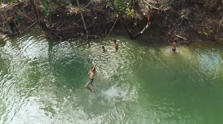 filipíny : CANDIJAY, BOHOL, PHILIPPINES - NOVEMBER 20, 2015: Filipina childrens dive and swim in the river
