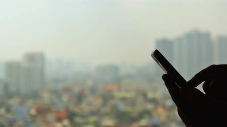 collaboration : Man dials the phone against the backdrop of the city from the window 1 Stock Footage
