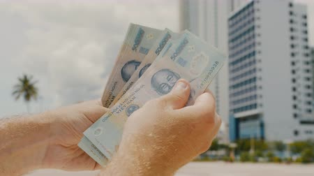 dolar : Man recounts Vietnamese money. Five hundred thousandth bills in the background of the city.