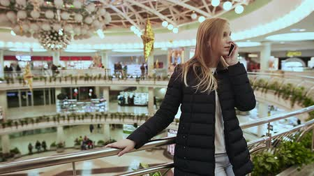 irodaház : Cute young girl in jacket, talking on a cell phone, ending the call in a big shopping center. Stock mozgókép