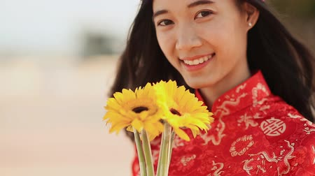 cortes : Beautiful Vietnamese girl in red traditional dress Ao Dai with yellow flowers. Close-up.